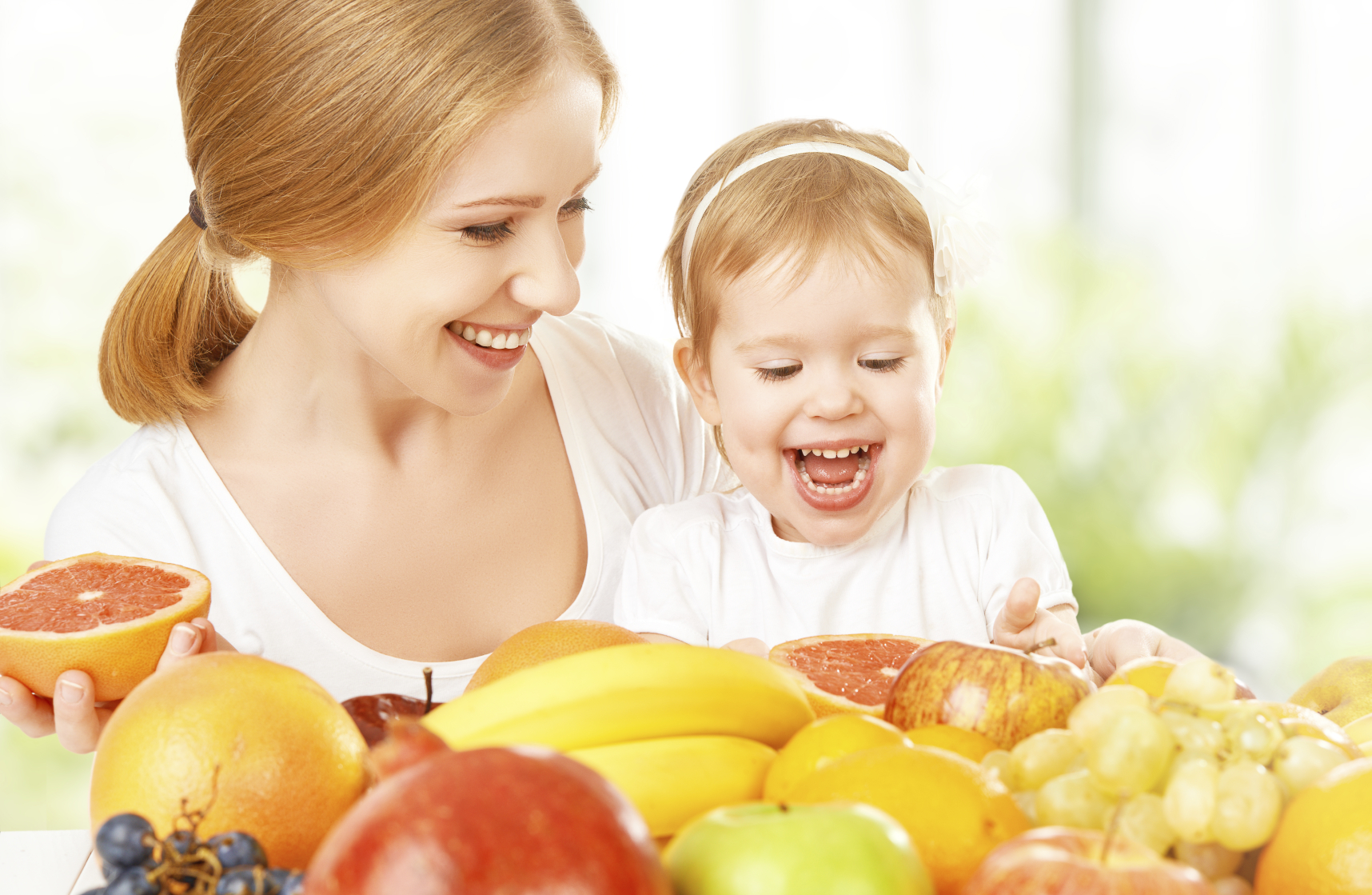 happy family mother and daughter little girl, eat healthy vegetarian food, fruit